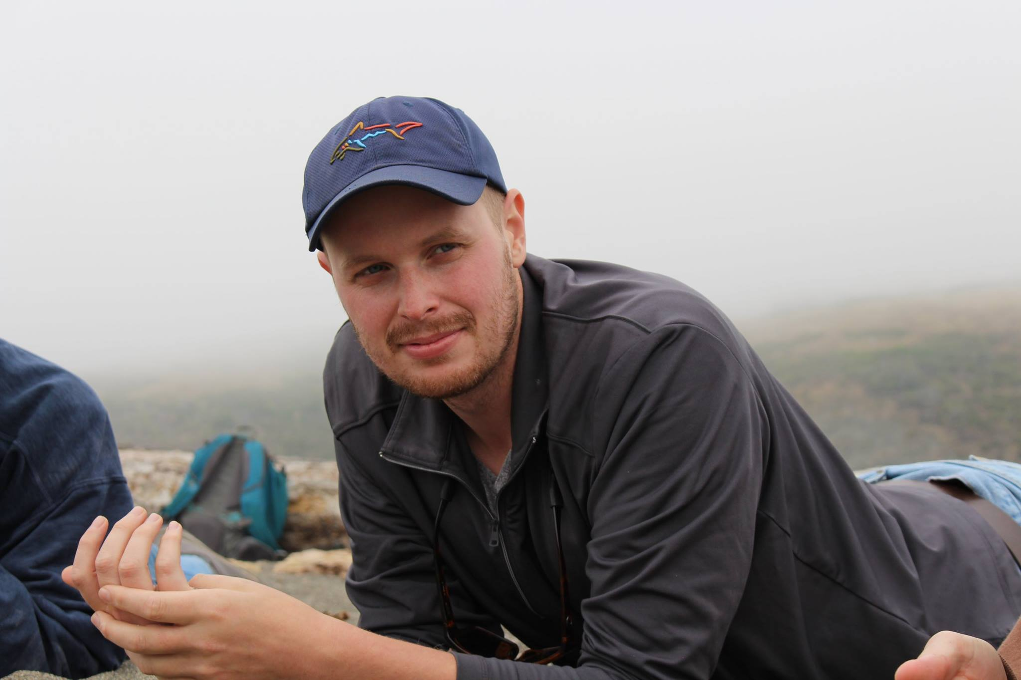 Program Associate Stephen McCloskey relaxing on top of a mountain